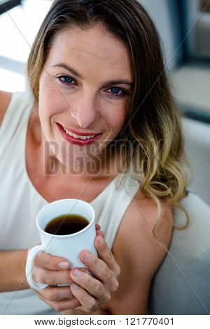 smiling woman, sitting on the couch, holding a cup of coffee