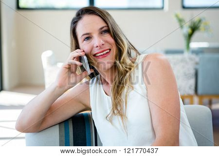 smiling woman sitting on a couch making a phone call