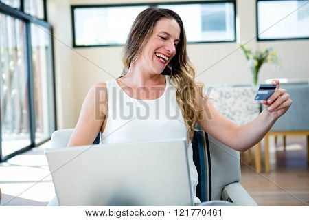 smiling woman sitting on a couch with her laptop and credit card
