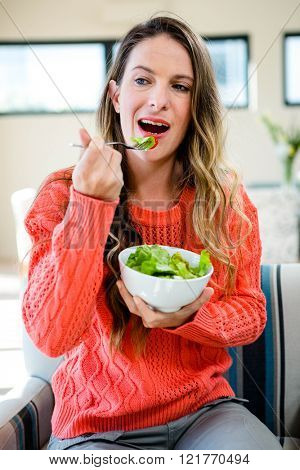 smiling woman , standing up, eating a bowl of fresh salad