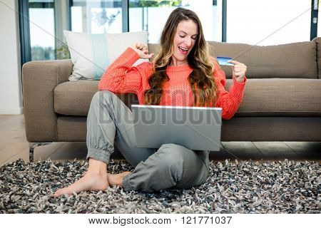 smiling woman sitting on the ground with her laptop and credit card