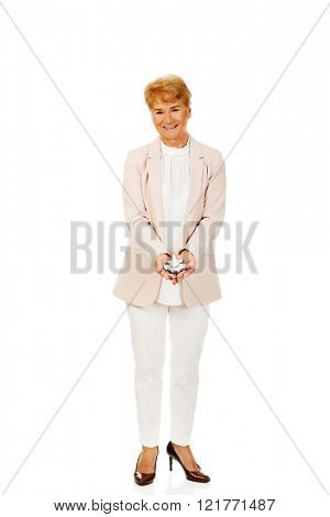 Smile elderly elegant woman holding a toy plane