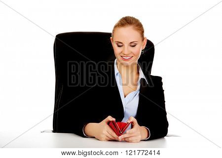 Smile business woman sitting behind the desk with wallet