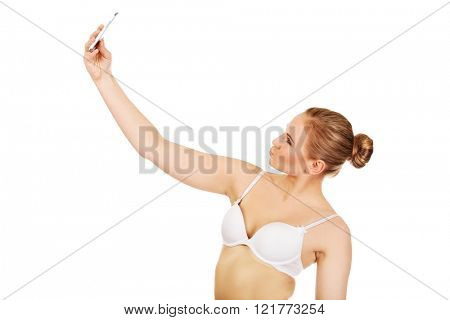 Young woman in underwear makes photo of herself