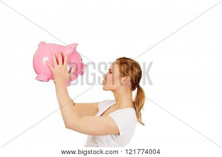Happy young woman kissing a piggybank