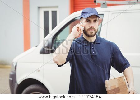 Delivery man making a phone call while holding a package