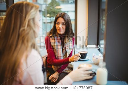 Pretty friends chatting over coffee in cafe