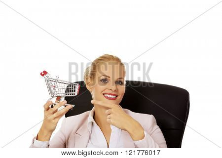 Smile business woman sitting behind the desk and holding small shopping cart