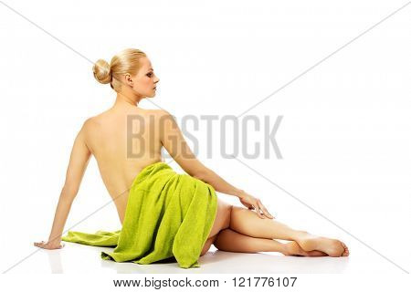 Young relaxed woman after bath or spa sitting on the floor wrapped in towel
