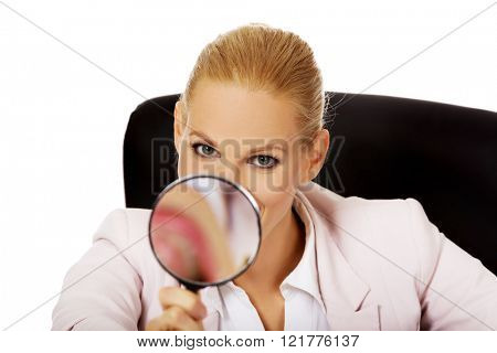 Smile business woman sitting behind the desk and looking into a magnifying glass
