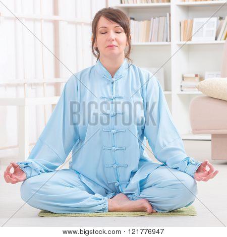 Beautiful woman meditating wearing professinal, oryginal chinese clothes at home