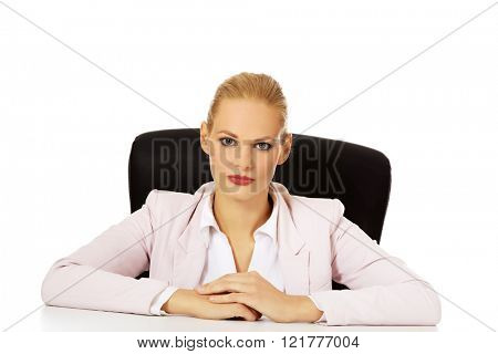 Young serious business woman sitting behind the desk