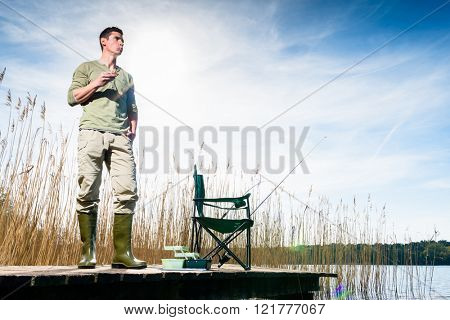 Angler standing on jetty having food for breakfast observing his fishing rod