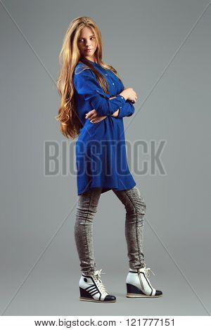 Full length portrait of a cute teenager girl with beautiful long hair posing over grey background. Youth fashion. Studio shot.