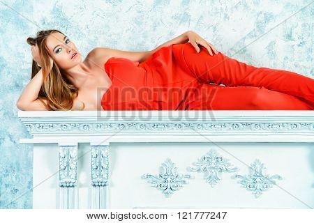 Gorgeous fashion model in bright red dress in vintage room with fireplace. Beauty, fashion. Love concept.