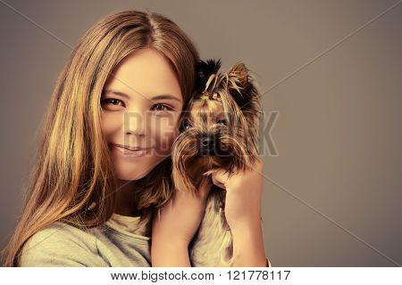 Happy girl holding her lovely yorkshire terrier dog.