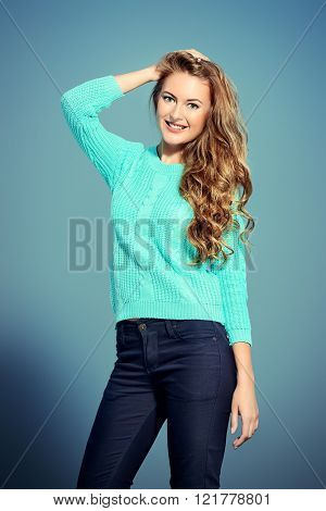 Pretty young woman with beautiful curly hair. Knitted clothes. Seasonal style.