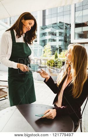 Smiling waitress serving a coffee to customer