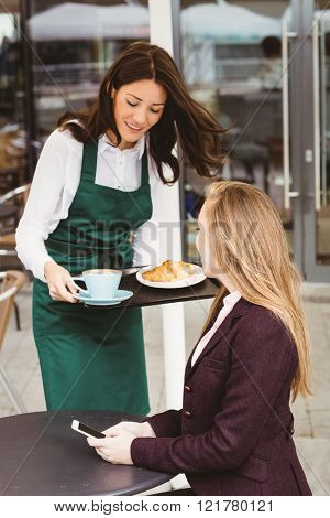 Smiling waitress serving a coffee and croissant to customer