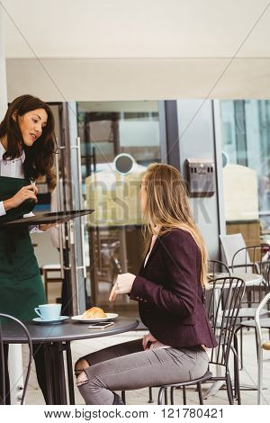 Woman talking with waitress in cafe