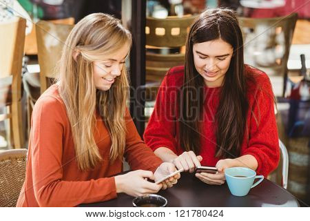 Friends using their smartphone in cafe