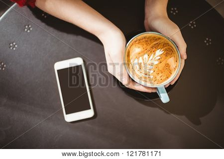 Woman holding a cup of coffee next to smartphone