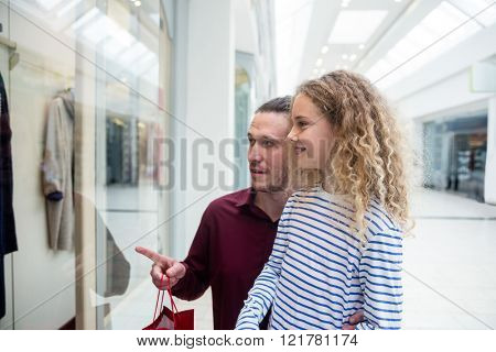 Happy father and daughter standing in front of shop window and looking at apparels