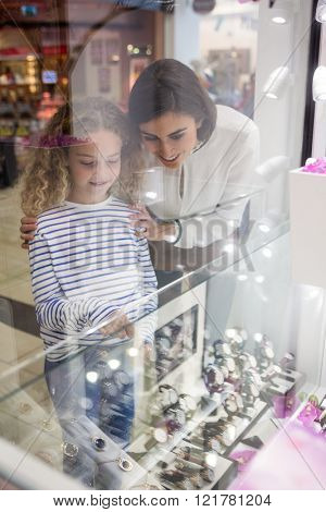 Mother and daughter selecting a wrist watch from a display of watches in shop
