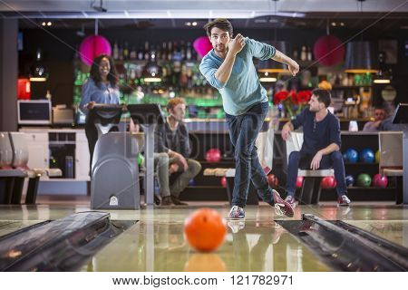 Group of friends are bowling and having fun, young man is throwing the ball at the bowling lane. poster