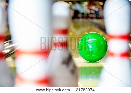 A bowling ball about to hit the pins on a 10 pin bowling alley, seen from the point of view of one of the pins
