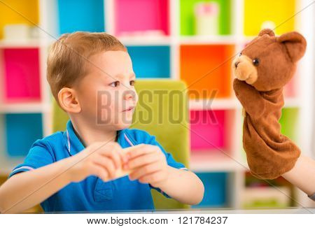 Young Boy Playing With Teddy Bear