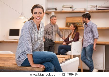 Young woman in casual sitting with crossed legs on table. Businesswoman sitting on table with colleagues in background. Happy young content business woman looking at camera and smiling.