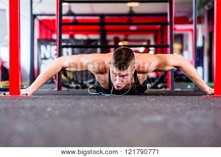 Man exercising doing push-up on floor of sport fitness gym
