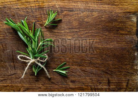 Rosemary bunch on rustic wood table, copy space