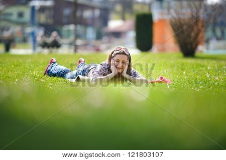 Young Woman Lying On The Grass In The Summer. Relaxing Outdoors Looking Happy And Smiling. Natural H