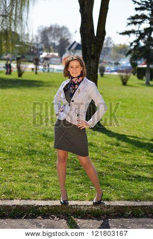 Beautiful Young Woman Posing Near A Green Tree On Nature, Enjoying The Nature