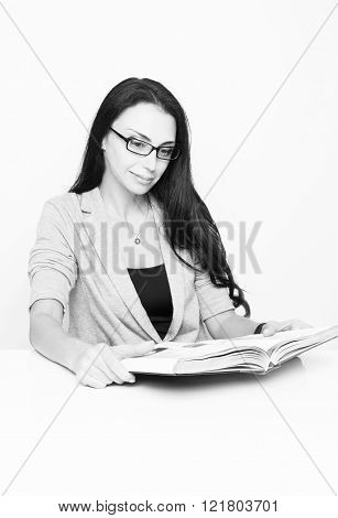 Young woman sits at her desk in a  office and looks  book