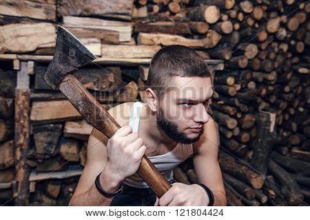 Man With An Ax Near Firewood Stock, Focus On Ax