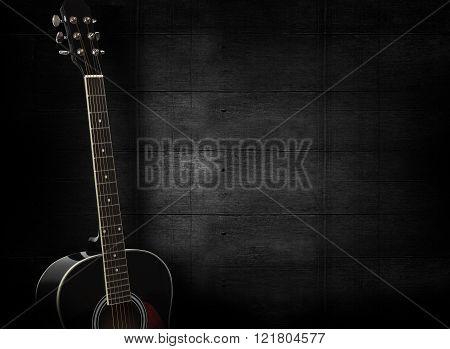 Black Acoustic Guitar On Dark Black Wooden Background.