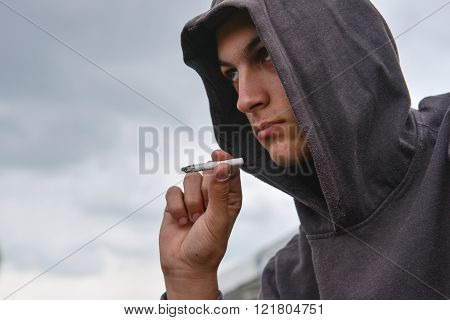 pensive and worried teenage boy with black hoodie is smoking cigarette outdoor. Harmful smoking concept poster