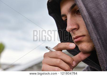 Pensive And Worried Teenage Boy With Black Hoodie Is Smoking Cigarette Outdoor. Harmful Smoking Conc