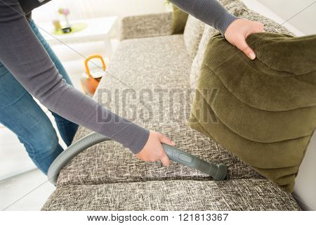Diligent hand of housewife vacuuming dust with vacuum cleaner