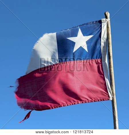 Broken Chilean flag flying over the blue sky