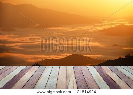 Empty top view of wooden table and view of sunset or sunrise on mountain background.