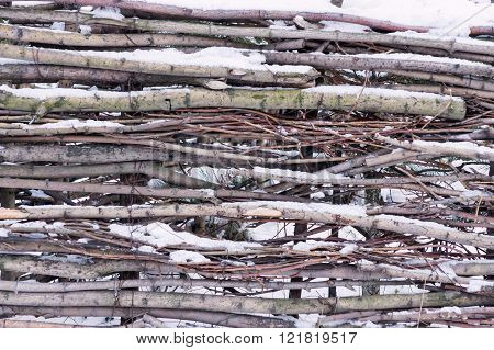 Snow-covered Wattle Fence From Wooden Branches