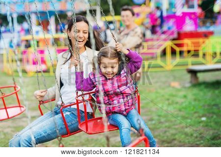 Mother and daughter at fun fair, chain swing ride