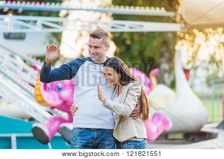 Parents at fun fair, waving their child taking ride