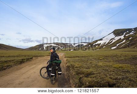 Biker rides on road at summer evening in Iceland. Travel and sport picture