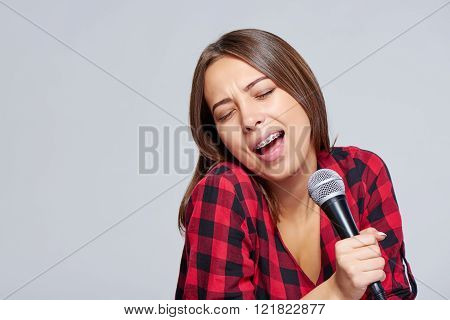 Emotional  girl singing a song in microphone