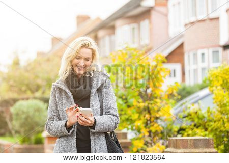 Adult woman looking at smart phone in front of some houses in London. She is a blonde woman on her early forties she looks candid and spontaneous. Lifestyle and technology concepts.** Note: Soft Focus at 100%, best at smaller sizes